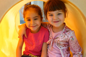 Two young girls with their arms around each other on yellow playground equipment