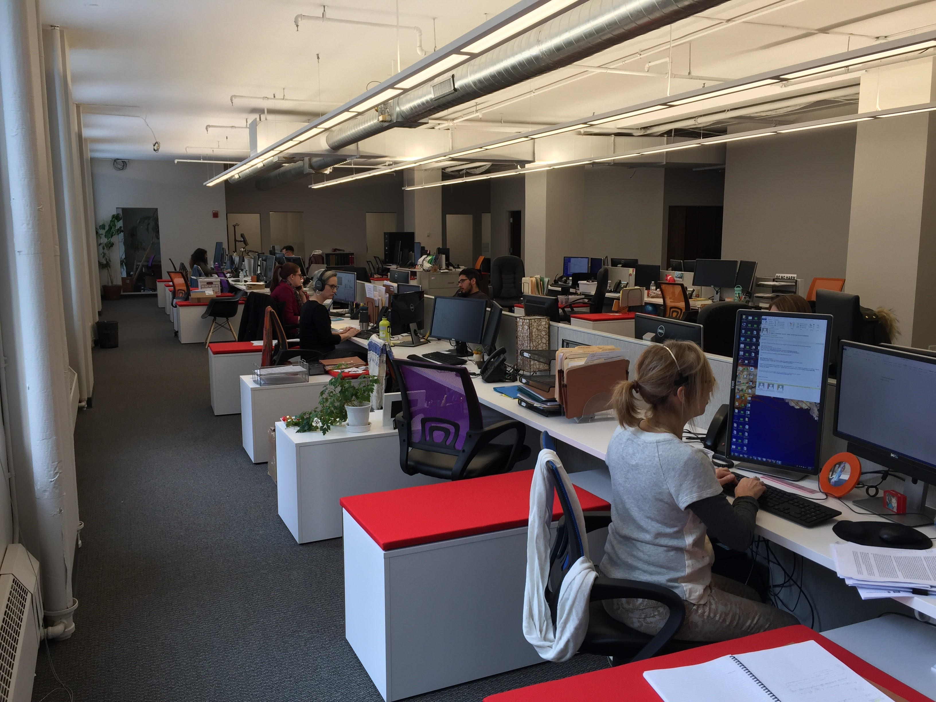 open office with white and red stations.