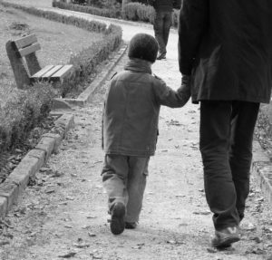 Young child holds hand of adult in black and white.