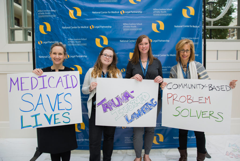 "At the MLP Summit, Carrie Chapman, Amanda Walsh, Sarah Hess, and Amy Zimmerman hold signs that say ""Medicaid Saves Lives,"" ""Trauma-Informed Lawyering,"" and ""Community-Based Problem Solvers."""