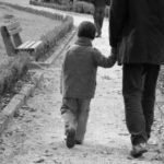 Black and white image; young child holds hand of adult